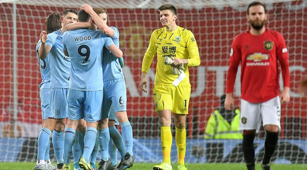 El portero inglés de Burnley, Nick Pope (C), reacciona cuando el delantero neozelandés de Chris Burnley, Chris Wood (3L) celebra después del partido de fútbol de la Premier League inglesa entre Manchester United y Burnley en Old Trafford en Manchester, al